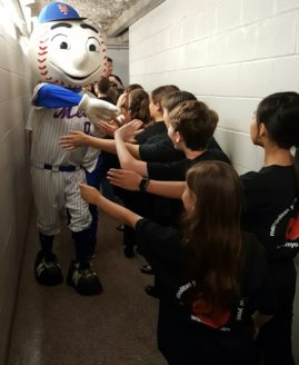 MYO Treble Choirs giving Mr. Met a high-five